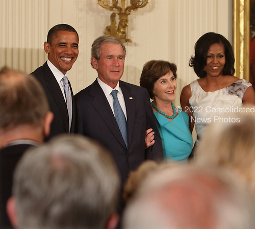 United States President Barack Obama (left), former U.S. President George W. Bush (2nd left), former first lady Laura Bush (2nd right) and first lady Michelle Obama pose for a photograph at the unveiling of the official White House Bush portraits at the White House in Washington, DC, May 31, 2012. .Credit: Chris Kleponis / CNP