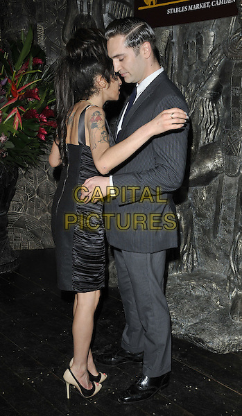 AMY WINEHOUSE & REG TRAVISS .Launch Party for 'Shaka Zulu' Private Members Club at Stables market, Camden,  London, England, UK,.August 4th 2010.full length black dress tattoos beige nude heels shoes grey gray suit tie side hug hugging back rear behind  white shirt couple boyfriend .CAP/CAN.©Can Nguyen/Capital Pictures.