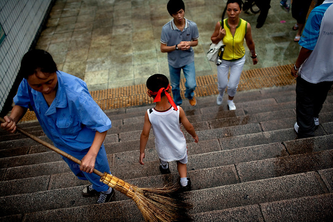 A city worker sweeps the water from a stairway after a fresh rainfall in Beijing, China on Sunday, August 10, 2008.  Kevin German