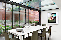 A modern conservatory extension with a glass roof and sliding glass doors, which give access to the garden. The room is furnished with a white dining table and grey green chairs.