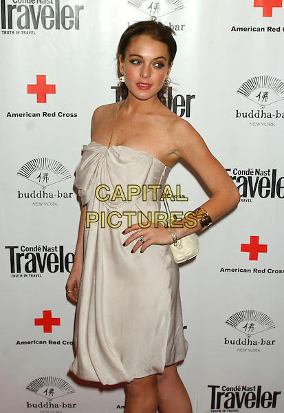 LINDSAY LOHAN.Attends Conde Nast Traveler Hot List Party, Buddha Bar, New York City, New York, USA,.April 18th 2006..half length strapless white dress bow hand on hip gold bracelet earrings jewellery.Ref: IW.www.capitalpictures.com.sales@capitalpictures.com.©Ian Wilson/Capital Pictures