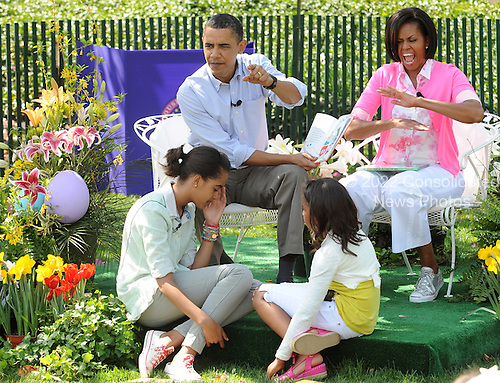 """United States President Barack Obama reads Dr. Suess' """"Green Eggs and Ham"""" on the South Lawn during the White House Easter Egg Roll in Washington on Monday, April 5, 2010. With him are First Lady Michelle Obama and their daughters Malia and Sasha.   .Credit: Roger L. Wollenberg / Pool via CNP"""