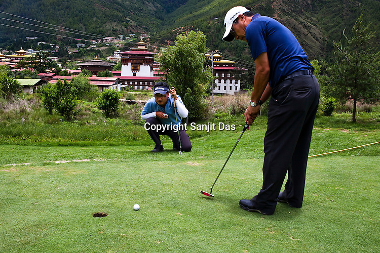 Golfers putt the ball on the greens at the Royal Thimphu Golf Course against the background of the Tashichho Dzong in Thimphu, Bhutan. Photo: Sanjit Das/Panos