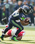 Seattle Seahawks running back Marshawn Lynch (24) is tripped up by Arizona Cardinals linebacker Kevin Minter (51) after a short gain at CenturyLink Field in Seattle, Washington on November 23, 2014. The Seahawks beat the Cardinals 19-3.  ©2014. Jim Bryant Photo. All Rights Reserved.
