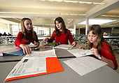 Selene Salem 12 and her twin sister Julianne, along with their little sister Sophia 8 (right), do their homework in the cafeteria of the Pennridge High School in Perkasie, Pa., during a wrestling match on Sunday February 26, 2006, in which their brothers, twins Sam and Jake 12 compete. The Salem children, 3 sets of twins, are from Russia. Sophia and twin Joseph were adopted at 11 months of age. The other twins were adopted just 20 months ago. All children are thriving in school and socially. photo by jane therese