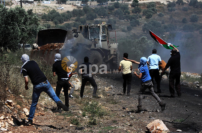 Palestinian protesters throw stones at an Israeli military bulldozer during clashes following a weekly protest against the expropriation of Palestinian land by Israel in the village of Kfar Qaddum, near Nablus, in the occupied West Bank on May 2, 2014. Photo by Nedal Eshtayah