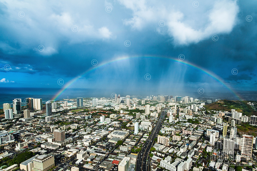 An aerial view of Ward and downtown Honolulu areas with a massive rainbow stretching over the freeway on O'ahu.