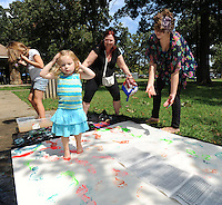 STAFF PHOTO ANDY SHUPE - Arianna Collins, 2, walks upon a banner with her feet covered in paint as her grandmother, Rose Collins of Fayetteville, center, and volunteer, Zoe Gray, 15, of West Fork help during the All Children's Fair: Welcoming Feet in Motion Sunday, Sept. 21, 2014, at Walker Park in Fayetteville. The event was organized by the Coalition to Stand With All the Children as a way to raise money for and awareness of refugee children at the U.S. boarder with Mexico.