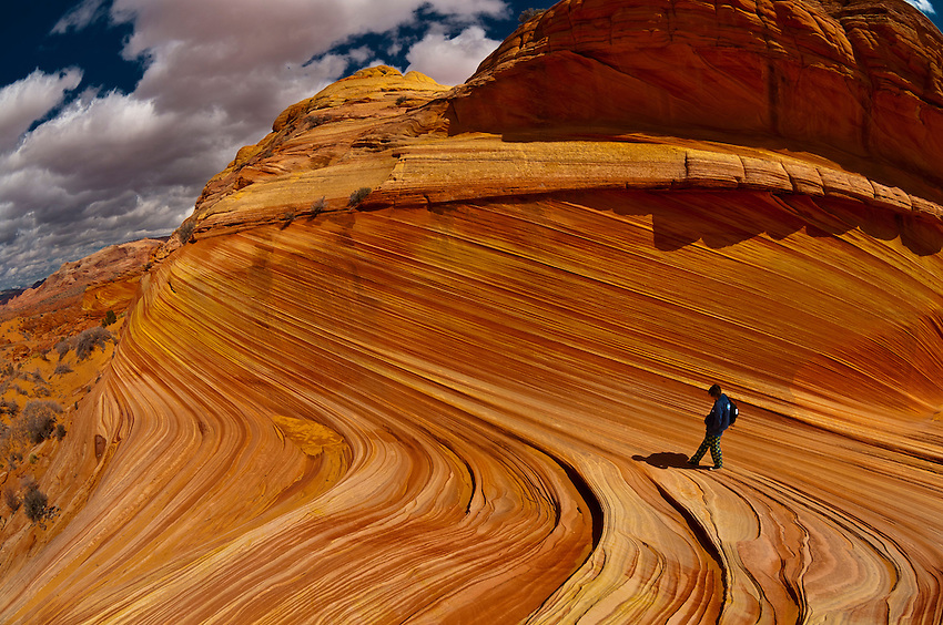 "Hikers exploring ""The Wave"", a 190 million year old Jurassic-age Navajo sandstone rock formation, Coyote Buttes, Paria Canyon-Vermillion Cliffs Wilderness Area, Utah-Arizona border, USA"