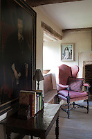 In the living room a 17th century wing-backed armchair covered in faded red brocade is arranged in front of the window seat next to the fireplace