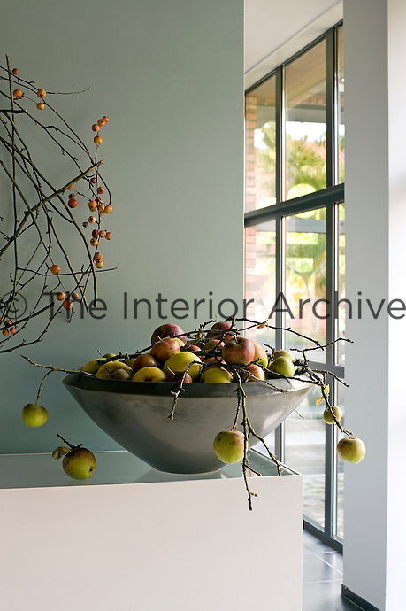 A contemporary ceramic bowl is filled with apples from the garden while a wreath of crab apples adorns the wall behind