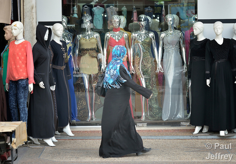 A woman walks by clothing on the street in the Zeitoun neighborhood of Gaza City, Gaza. Residents of the Palestinian territory are still reeling from the death and destruction of the 2014 war with Israel, and the continuing siege of the seaside territory by the Israeli military.
