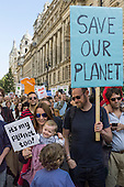 A family marches holding placards; the father's says 'Save Our Planet', the baby has 'it's my planet too!'; Climate Change demonstration, London, 21st September 2014. © Sue Cunningham