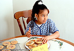 7 year old girl  taking forbidden homemade cookie from plate Hispanic Dominican horizontal