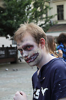 male participant in the Zombi walk in prague may 2014. Wearing blue t-shirt with white print. Have teeth painted on the cheek.