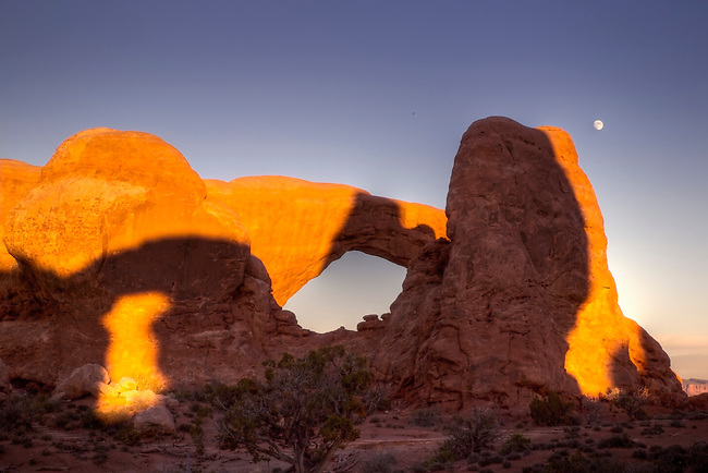 A moon and a silhouette of Turret Arch appear at sunset at South Window at Arches National Park, Utah