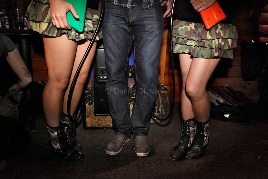 Big Buck Girls Andrea Miele, 23, left, and Alicia Patterson, 24, pose for a portrait with reigning Big Buck world champion Alex DerHohannesian, 30, at The Black Bear Lodge in Manhattan, which hosted an official Big Buck Party on Thursday April, 28, 2011. Fans of the popular hunting arcade game were invited to test their skill against other Big Buck Hunter fans to compete for prizes, enter to win raffle merchandise and meet Big Buck Girls...Danny Ghitis for The New York Times