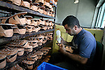 Palestinian worker glues the sole of a new leather sandal in a shoe factory in the West Bank City of Hebron, on Aug. 31, 2010. Hebron, which is known for its leather industries for more than 80 years, exports more than 100,000 pairs of shoes every year, according to statistics from the Palestinian Trade and Commerce Chamber . Photo by Eyad Jadallah