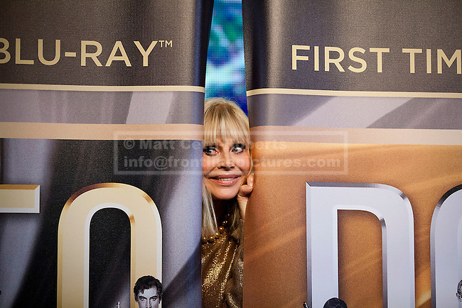 24/09/2012. LONDON, UK. Actress Britt Ekland, who played Bond Girl 'Goodnight' in 'The Man with the Golden Gun' is seen peeking through curtains inside HMV's Oxford Street store in London, today (24/09/12) during a photocall. The stars were in London during the final leg of a UK tour to promote the Bond 50 Blu-Ray collection.  Photo credit: Matt Cetti-Roberts