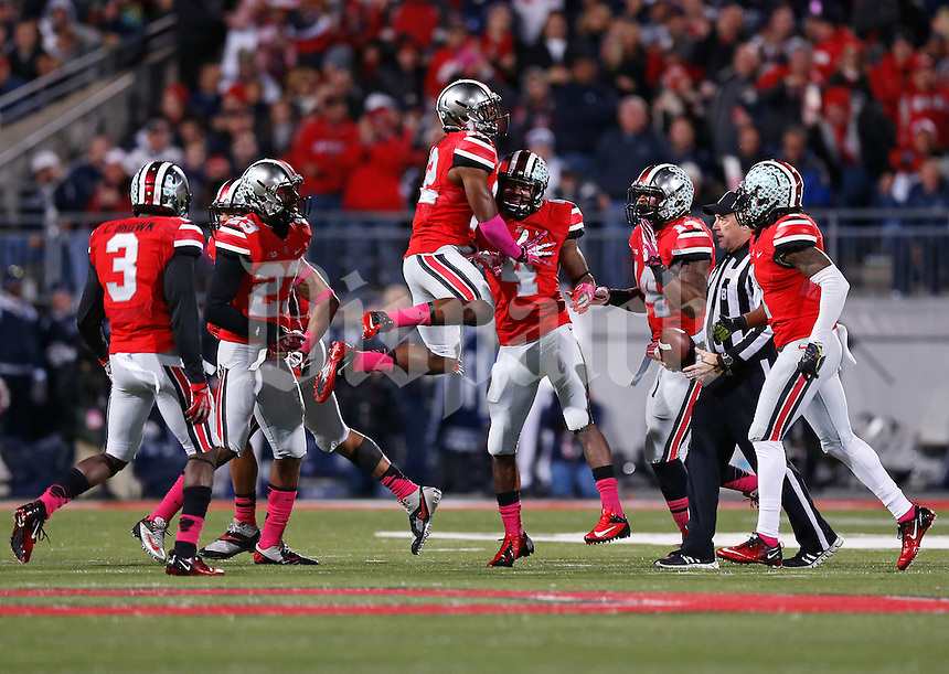 Ohio State Buckeyes cornerback Doran Grant (12) leaps into Ohio State Buckeyes safety C.J. Barnett (4) after Barnett intercepted a pass during the first half of the NCAA football game at Ohio Stadium in Columbus on Oct. 26, 2013. (Adam Cairns / The Columbus Dispatch)