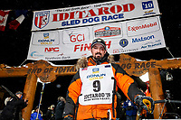 Pete Kaiser stands at his sled at the Nome finish line shortly after winning the 2019 Iditarod Trail Sled Dog Race. Pete's winning time is 9 days 12 hours 39 minutes and 6 seconds<br /> <br /> Photo by Jeff Schultz/  (C) 2019  ALL RIGHTS RESERVED