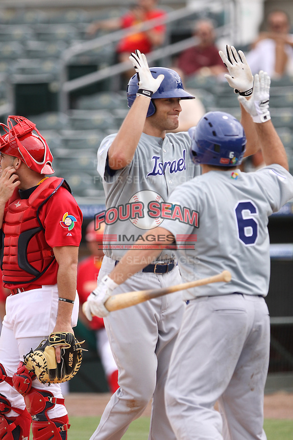 Nate Freiman of Team Israel meets with Cody Decker during a game against Team Spain during the World Baseball Classic preliminary round at Roger Dean Stadium on September 21, 2012 in Jupiter, Florida. Team Israel defeated Team Spain 4-2. (Stacy Jo Grant/Four Seam Images)