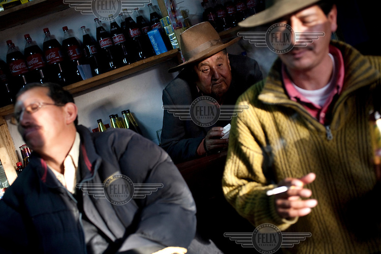 People smoke at a bar during the Yawar Fiesta in the town of Coyllurqui in the Peruvian Andes on Independence Day.