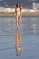 Natasha Jenkins enjoys the unusually warm weather on the beach in Swansea Bay, Wales, UK. Monday 25 February 2019