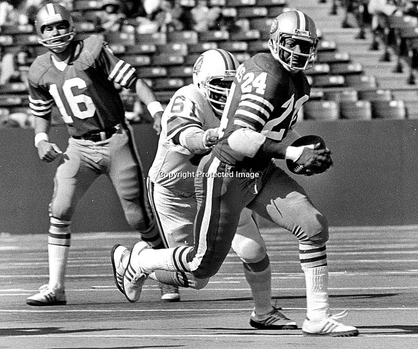S.F. 49er Delvin Williams with hand-off from Jim Plunkett, Tampa Bay Buccaneers Dewey Selmon.<br /> (1977 photo/Ron Riesterer)