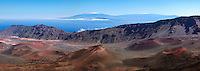 Panorama photo of the multiple cinder cones in the crater of Haleakala National Park on Maui in the foreground with unique view of snow on the mountain tops of Mauna Kea and Mauna Los on the Big Island of Hawaii