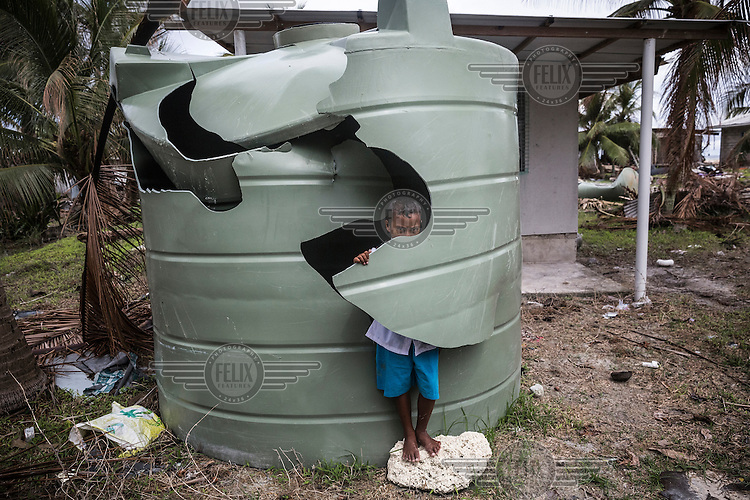 Utime, nine, stands beside a damaged water tank in Tanrake village on the Fenua Tapu islet, Nui atoll. Nui was affected by storm surges caused by Cyclone Pam in which 12 houses were completely destroyed and 110 homes badly damaged. 71 families (40% of the population) from Nui were displaced and were living in evacuation centres or with other families. According to Tuvalu Prime Minister Enele Sopoaga estimated 45 percent of the nation's nearly 10,000 people were displaced.