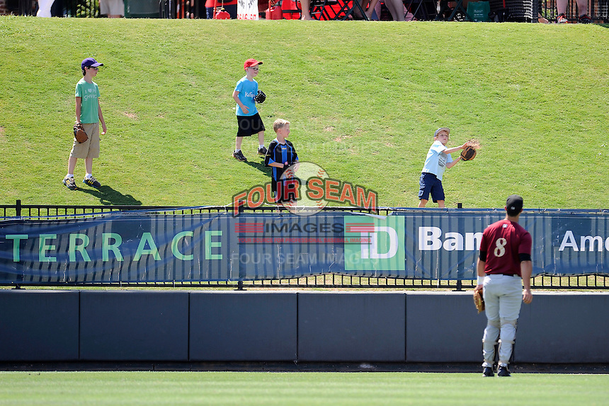 Catcher Colton Plaia (8) of the Savannah Sand Gnats plays catch with young fans in the left field berm before a game against the Greenville Drive on Sunday, June 22, 2014, at Fluor Field at the West End in Greenville, South Carolina. Greenville won, 7-3. (Tom Priddy/Four Seam Images)