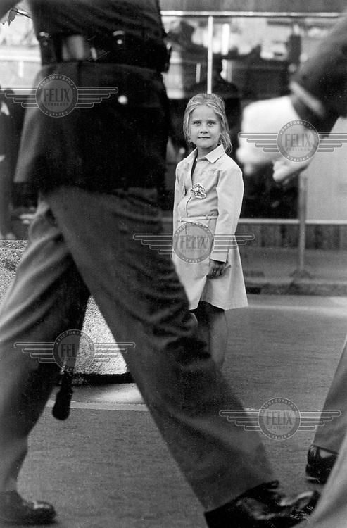 A young white girl watches a soldiers marching during military parade through the city centre.