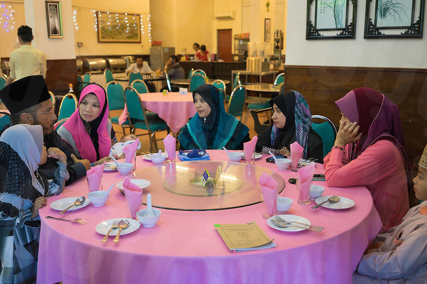 """January 15, 2015 - Rawang (Malaysia). Global Ikhwan's CEO Lokman Hakim, has lunch with his 4 wives and 3 of his 27 children in a Chinese restaurant in Rawang. Although polygamy is legal in Malaysia, it is rarely practiced in the open or with the knowledge and approval of all the wives involved in such a relationship. However,Global Ikhwan - only employs women, who view polygamy as the integral element of """"the Islamic way of life."""" © Thomas Cristofoletti / Ruom"""