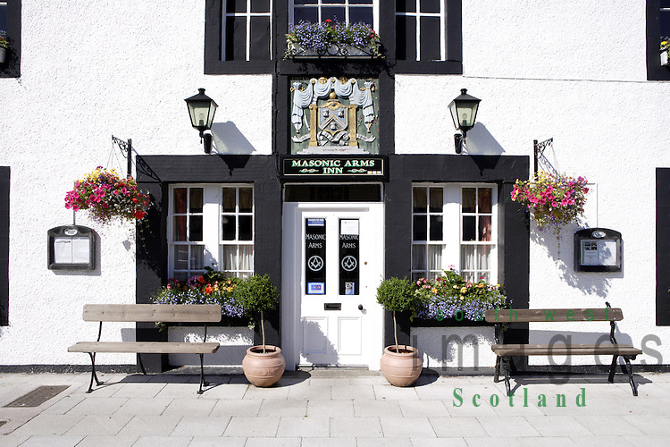 The front door of the Masonic Arms Inn summer hanging baskets, pots and window boxs full of flowers Gatehouse of Fleet Galloway Scotland UK