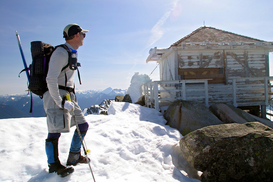 Man walking on snow towards Mount Pilchuck Lookout, Snohomish County, Cascade Mountains, Washington, USA