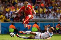 Kevin De Bruyne of Belgium hurdles Vasiliy Berezutskiy of Russia