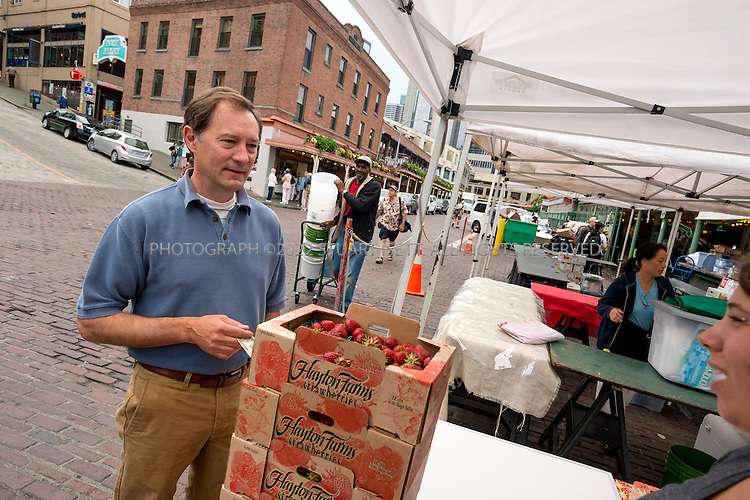 7/13/2012--Seattle, WA, USA..Peter Steinbrueck buying strawberries at Pike Place Market...©2012 Stuart Isett. All rights reserved.