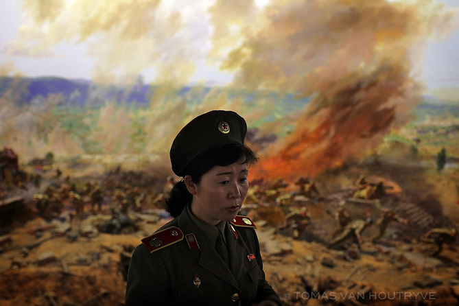 A North Korean military woman stands in front of a battle scene depicting Americans being defeated by North Korean troops in Pyongyang, North Korea (DPRK) on 20 August, 2007.
