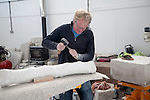 Sculptor working on local Portland stone in a community studio space on the Isle of Portland, Dorset, England, UK