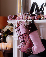 Handmade taffeta Christmas stockings hang from the mantelpiece and are decorated with glass beads