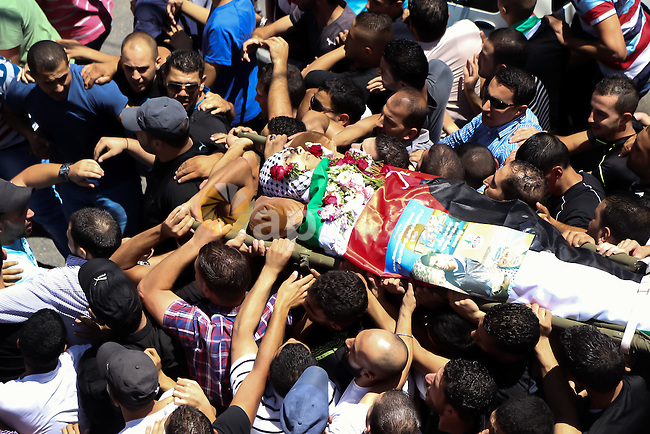 "Mourners carry the body of Palestinian man Mohammed al-Araj, who medics said was killed by Israeli troops, during his funeral at Qalandia refugee camp near the West Bank city of Ramallah July 25, 2014. Israeli soldiers shot and killed Palestinian protester al-Araj, and wounded about 200 on Thursday in confrontations with several thousand people demonstrating in the occupied West Bank against a 17-day-old Israeli offensive in Gaza, Palestinian medical officials said. The Israeli military confirmed troops had used ""riot dispersal means"" against protesters who threw rocks and firebombs at them and blocked a road with burning tyres. Photo by Shadi Hatem"