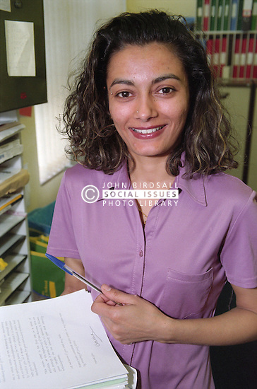 Portrait of young woman in school office holding papers and pen,