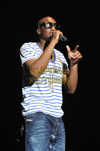 Loick Essien .Performing live at the 'Girlguiding UK  Big Gig' at Wembley Arena, London, UK, 1st October 2011..music concert  live on stage half length blue and white striped t-shirt sunglasses jeans microphone  necklace hand singing .CAP/MAR.© Martin Harris/Capital Pictures.