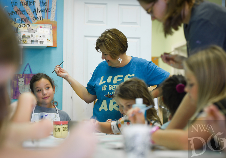 NWA Democrat-Gazette/CHARLIE KAIJO Imagine Studios owner Melanie Hewins (center) helps Katie Segura, 7, of Rogers (left) with an art project during an art camp, Monday, August 5, 2019 at Imagine Studios in Rogers.<br /> <br /> Imagine Studios owner Melanie Hewins held an art camp called Unicorn Dreams. Kids decorated unicorn themed plates and unicorn and rainbow magnets. The camp runs till Thursday. Kids learn how to use acrylic paints and water colors and canvas and ceramic painting.