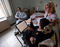 Kara helps a client in a nursing home prepare documents to receive help from Arise with finding an independant living arrangement. Photo by James R. Evans ©
