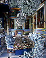 Pale blue panelling punctuated with gilt-framed portraits is picked up in the colour scheme of the soft furnishings in this impressive dining room