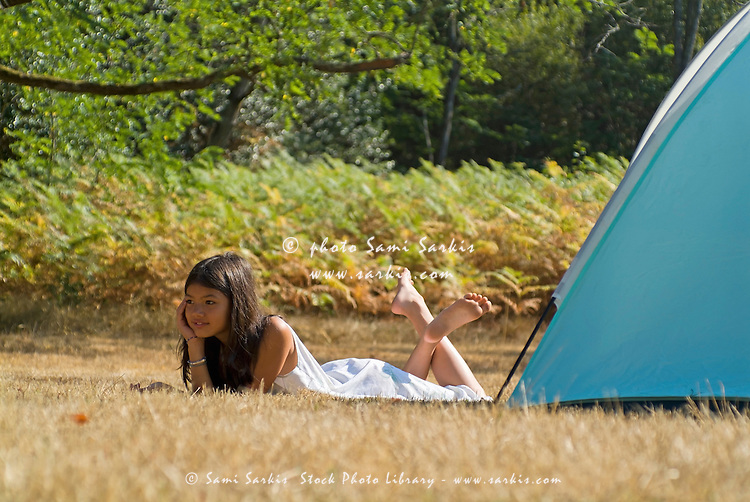 Young Asian girl lying down beside a c&ing tent in the Landes Forest Aquitaine & Young Asian girl lying down beside a camping tent in the Landes ...