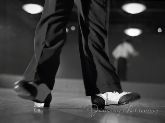 A man tap dances in his studio, balancing on the heels of his shoes