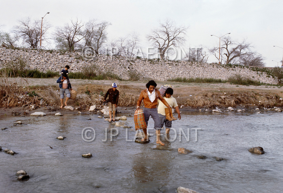 El Paso, TX. March 11th, 1983. <br /> The border patrol watches as many Mexicans made their daily journey accross the Rio Grande River into Del Rio, to work for the day, and return to Mexico the same evening.